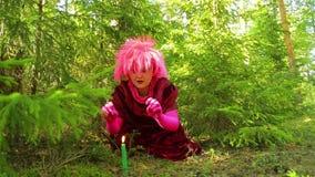 Een sympathieke heks in een rituele kledij tovert een kaars in het bos stock footage