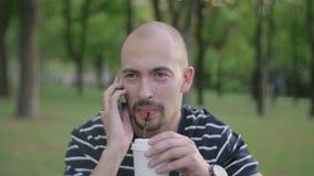 Een sympathieke mensenzitting op een gazon in een stadspark het drinken koffie van een beschikbaar glas en het spreken op zijn mo stock videobeelden
