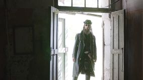 Een taaie kerel in een zwarte regenjas opent de deur voor een verlaten ruimte met een schop stock video