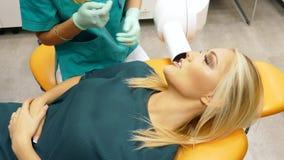 Een tandarts neemt een röntgenstraal van vrouwelijke patienttanden stock video