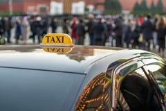 Een taxi op de stoep van een grote straat met grote opstoppingen wordt geparkeerd, de auto wijst op de lichten van de nachtstad d Stock Afbeelding