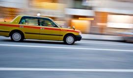 Een taxiauto in motieonduidelijk beeld Stock Afbeeldingen