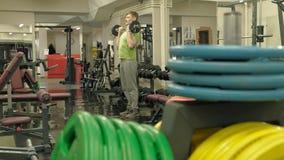 Een te zware mens heft een ez op barbell terwijl status bij de gymnastiek Oefening voor bicepsen Geschiktheid Gezonde Levensstijl stock videobeelden