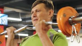 Een te zware mens heft een ez op barbell terwijl status bij de gymnastiek Oefening voor bicepsen Geschiktheid Gezonde Levensstijl stock video