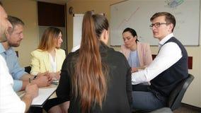 Een team van bureauwerknemers die op een creatief project in bestuurskamer bespreken Een groep jonge leden van personeel het werk stock video
