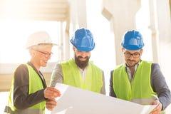 Een team van jonge vrouwen en twee jonge mannen bekijkt de bouw van plannen stock foto
