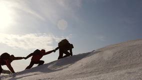 Een team van reizigers gaat naar zijn doel, die moeilijkheden overwinnen de toeristen houden handen binnen beklimmend sneeuwberg stock video