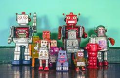 Een team van retro robots op een houten vloer Stock Foto