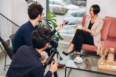 Een team van TV toont het praatje van een populaire nodel met een presentator registreert stock afbeelding