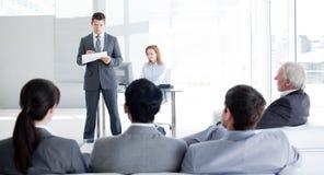 Een teamleider die aan zijn collega's spreekt