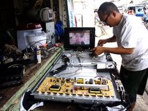 Een technicus van de elektronikareparatiewerkplaats werkt aan een vlakke het schermtv Stock Foto's
