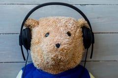 Een teddybeer in de hoofdtelefoons op houten achtergrond Stock Afbeeldingen