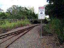 Een teken die geen toegang voor gevaarlijke activiteiten op een spoorwegspoor tonen door een rivier Stock Foto