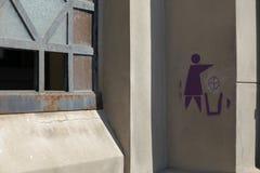 Een teken van recyclerende vrouw op de muur stock afbeeldingen