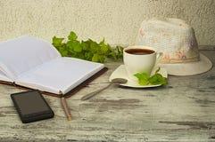 Een telefoon, een kop van koffie en een hoed royalty-vrije stock foto