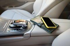 Een telefoon en een beurs liggen op een elleboog-rest in de salon van auto stock afbeeldingen