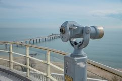 Een telescoop met een brug en een blauwe overzees en hemel op de achtergrond Stock Afbeelding