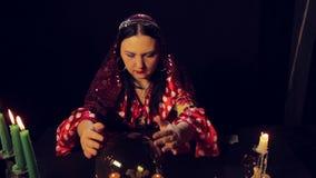 Een teller van het zigeunerfortuin bij een candlelit lijst is op een magisch kristal benieuwd stock video