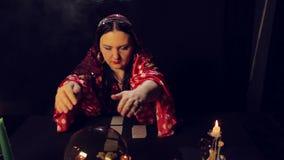 Een teller van het zigeunerfortuin bij een lijst door kaarslicht leest de toekomst in een magisch kristal in rook stock video