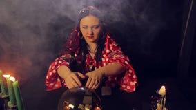 Een teller van het zigeunerfortuin bij een lijst door kaarslicht leest de toekomst in een magisch kristal in rook stock videobeelden