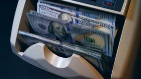Een teller werkt met dollarrekeningen, berekenend hen stock videobeelden