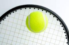 Een tennisbal is op de racket Stock Foto