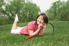 Een tennismeisje zeer gelukkig op gras Stock Afbeeldingen