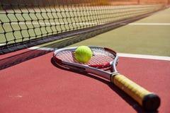 Een tennisracket en een nieuwe tennisbal op een vers geschilderde tennisbaan Stock Afbeelding
