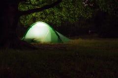 Een tent onder een oude eik in de nacht Stock Foto