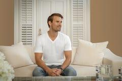 Een terloops geklede knappe mens zit in een moderne woonkamer stock foto