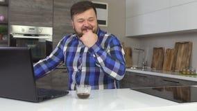 Een tevreden en vrolijke mens met een baard werkt bij laptop in een moderne keuken en lach, langzame motie, technologie stock videobeelden