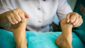 Een therapeut geeft een massage op de geduldige voeten van ` s stock foto