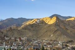 Een Tibetaanse tempel op een berg boven de stad met een gloed van de het plaatsen zon royalty-vrije stock afbeeldingen