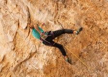 Een tiener bereikt in een krijtzak om haar handen met krijt te bestrooien als voorbereiding op bergbeklimming stock foto's