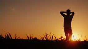 Een tiener bewondert de zonsondergang Zich bevindt op het gebied, zet hij zijn handen achter de rug van zijn hals, de achtermenin stock videobeelden