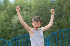 Een tiener in een T-shirt en borrels viert de overwinning royalty-vrije stock fotografie