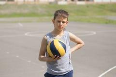 Een tiener in een vest houdt een bal in zijn hand royalty-vrije stock fotografie