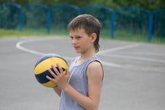 Een tiener in een vest houdt een bal in zijn hand stock fotografie