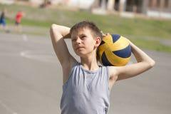 Een tiener in een vest houdt een bal in zijn hand royalty-vrije stock afbeeldingen
