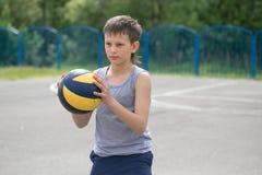 Een tiener in een vest houdt een bal in zijn hand royalty-vrije stock afbeelding