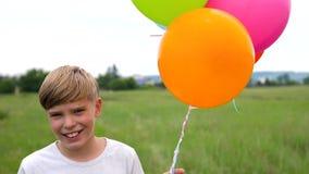 Een tiener houdt ballons De zomervakantie in aard dichtbij het meer Viering en pret Kind` s verjaardag stock videobeelden