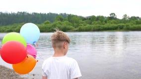 Een tiener houdt ballons De zomervakantie in aard dichtbij het meer Viering en pret Kind` s verjaardag stock footage