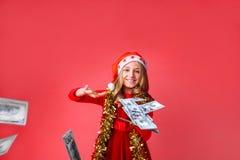 Een tiener in een Kerstmanhoed en met klatergoud op haar hals, met dollars in haar handen, besteedt geïsoleerd geld aan een rode  stock afbeeldingen