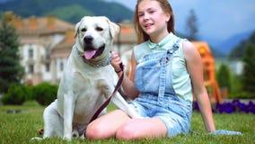 Een tiener koestert en speelt met haar favoriete hond in het park 4K stock videobeelden