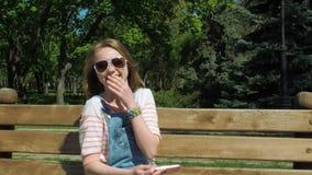 Een tiener maakt selfie Meisje met een telefoon in het park Een meisje met sproeten en overall wordt gefotografeerd stock video