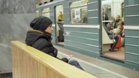 Een tiener met een smartphone in zijn handen zit op een bank in een metropost De kerel in de winterkleren is aanwezig stock videobeelden