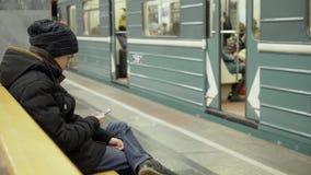 Een tiener met een smartphone in zijn handen zit op een bank in een metropost De kerel in de winterkleren is aanwezig stock footage