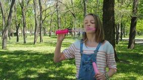 Een tiener met zeepbels in het park Meisje op een zonnige dag in de verse lucht Een kind speelt met binnen bellen stock video
