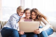 Een tiener, een moeder en een grootmoeder met laptop thuis royalty-vrije stock afbeelding