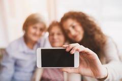 Een tiener, een moeder en een grootmoeder met smartphone thuis stock fotografie
